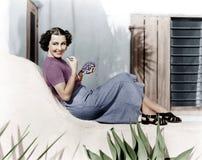 Sammanträde för ung kvinna på en terrass som ler och äter druvor (alla visade personer inte är längre uppehälle, och inget gods f arkivfoto