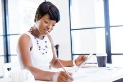 Sammanträde för ung kvinna på ett skrivbord i ett kontor och ett arbete på ritning Royaltyfri Fotografi