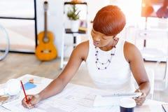 Sammanträde för ung kvinna på ett skrivbord i ett kontor och ett arbete på ritning Royaltyfria Foton