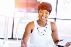 Sammanträde för ung kvinna på ett skrivbord i ett kontor och ett arbete på ritning Royaltyfria Bilder
