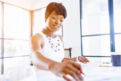 Sammanträde för ung kvinna på ett skrivbord i ett kontor och ett arbete på ritning Royaltyfri Foto