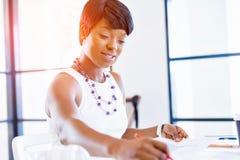 Sammanträde för ung kvinna på ett skrivbord i ett kontor och ett arbete på ritning Arkivbild