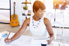 Sammanträde för ung kvinna på ett skrivbord i ett kontor och ett arbete på ritning arkivfoto