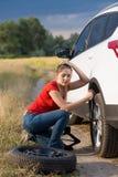 Sammanträde för ung kvinna på hennes bil med det plana gummihjulet som försöker att skruva av hjulmuttrar Royaltyfri Bild