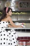 Sammanträde för ung kvinna på matställeräknaren Royaltyfri Fotografi