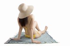Sammanträde för ung kvinna på mattt med bikinin Royaltyfri Foto
