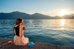 Sammanträde för ung kvinna på pir på soluppgång Royaltyfri Fotografi