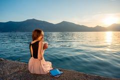 Sammanträde för ung kvinna på pir på soluppgång Fotografering för Bildbyråer