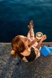 Sammanträde för ung kvinna på pir på soluppgång Arkivbild
