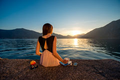 Sammanträde för ung kvinna på pir på soluppgång Royaltyfria Bilder