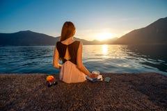 Sammanträde för ung kvinna på pir på soluppgång Royaltyfria Foton