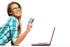 Sammanträde för ung kvinna på skrivbordet som direktanslutet shoppar Royaltyfri Bild