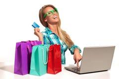 Sammanträde för ung kvinna på skrivbordet som direktanslutet shoppar Fotografering för Bildbyråer