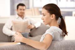 Sammanträde för ung kvinna på soffaman i bakgrund fotografering för bildbyråer