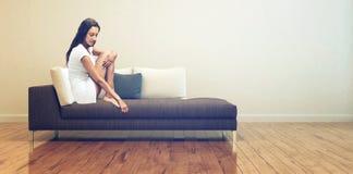 Sammanträde för ung kvinna på soffan på vardagsrummet Royaltyfri Foto