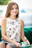 Sammanträde för ung kvinna på soffan som dricker te från koppen i ett kontor fotografering för bildbyråer