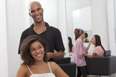Sammanträde för ung kvinna på stol med frisöranseende bakom royaltyfri fotografi