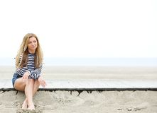 Sammanträde för ung kvinna på tänka för strand Arkivbild