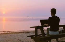 Sammanträde för ung kvinna på tabellen med en bärbar dator royaltyfri foto