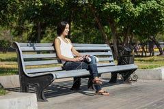 Sammanträde för ung kvinna på trappan och lyssna till musik Fotografering för Bildbyråer