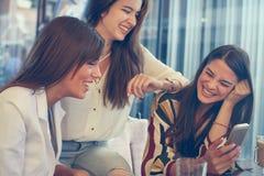Sammanträde för ung kvinna tre i kafé genom att använda den smarta telefonen Royaltyfri Foto