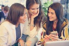 Sammanträde för ung kvinna tre i kafé genom att använda den smarta telefonen och ha f Royaltyfria Bilder