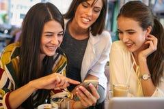 Sammanträde för ung kvinna tre i kafé genom att använda den smarta telefonen och ha f Arkivbilder