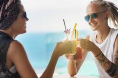 Sammanträde för ung kvinna två i kafét som dricker smoothien arkivbilder