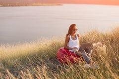 Sammanträde för ung kvinna utomhus i äng på bärbara datorn arkivfoto