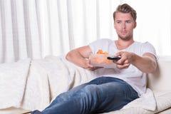 Sammanträde för ung man för stående på soffan och äta chiper och zapping Royaltyfri Bild