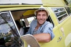 Sammanträde för ung man i campa bil för tappning fotografering för bildbyråer