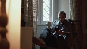 Sammanträde för ung man i fåtölj i vardagsrum och användasmartphone Attraktiv manlig bläddrande internet, drinkkaffe lager videofilmer