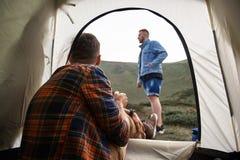 Sammanträde för ung man i tältet och se hans vän royaltyfria bilder