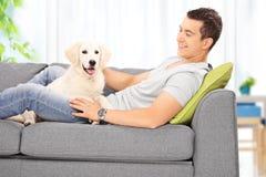 Sammanträde för ung man med hans valp på en soffa hemma Royaltyfri Bild