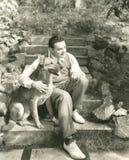 Sammanträde för ung man med hunden på moment utomhus Royaltyfri Foto