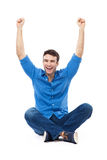 Sammanträde för ung man med lyftta armar Fotografering för Bildbyråer