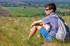 Sammanträde för ung man med ryggsäcken och se den härliga sikten, turismbegrepp royaltyfri fotografi