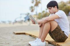 Sammanträde för ung man på den hållande minnestavlan för strand Fotografering för Bildbyråer
