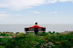Sammanträde för ung man på en bänk som ser havet Arkivfoton