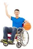 Sammanträde för ung man på en rullstol och ett innehav en basket Royaltyfria Foton