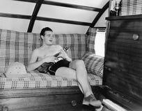 Sammanträde för ung man på en soffa och spela en gitarr (alla visade personer inte är längre uppehälle, och inget gods finns Leve arkivfoto