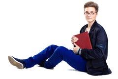 Sammanträde för ung man på golv och läsning en bok royaltyfri fotografi