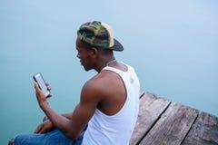 Sammanträde för ung man på kanten av en pir och se hans mobiltelefon uppmärksamt arkivfoto