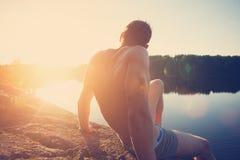 Sammanträde för ung man på klippan nära sjön och se långt borta på solnedgången arkivfoto