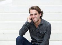 Sammanträde för ung man på moment med mobiltelefonen Royaltyfri Foto