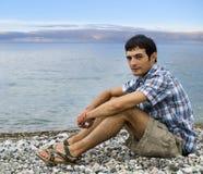 Sammanträde för ung man på Pebble Beach under solnedgång Arkivfoton