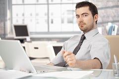 Sammanträde för ung man på skrivbordet genom att använda bärbara datorn royaltyfri bild