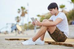 Sammanträde för ung man på stranden genom att använda minnestavlan Arkivfoto