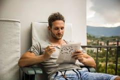 Sammanträde för ung man som gör ett korsordpussel royaltyfri foto
