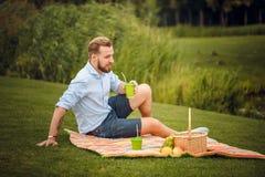 Sammanträde för ung man som har en picknick utomhus royaltyfri foto